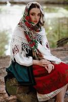 jovem em um vestido bordado tradicional sentada em um banco perto do lago