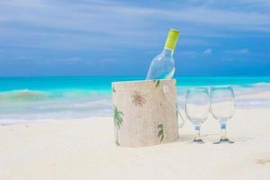 vinho branco e taças na praia foto