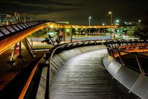 ponte de madeira com luzes em uma cidade à noite