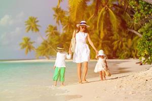 mãe e dois filhos caminhando em uma praia tropical foto