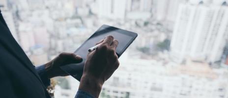 empresário trabalhando com tablet com o fundo da cidade foto