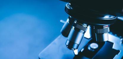 close-up de microscópio científico com lente de metal, análise de dados em laboratório