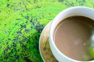 café quente na mesa verde foto