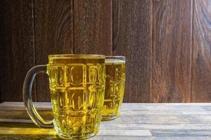 duas canecas de vidro com cerveja foto