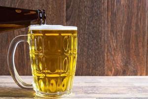 derramando cerveja em uma caneca foto