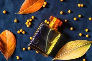 frasco de perfume com folhas douradas foto