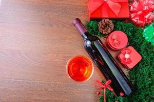 copo de vinho e garrafa com caixa de presente de natal foto