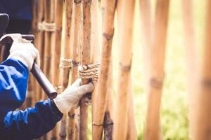 carpinteiro com martelo batendo pregos no bambu foto