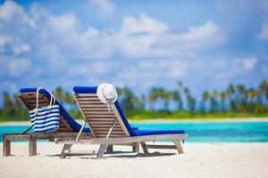 duas espreguiçadeiras em uma praia tropical foto