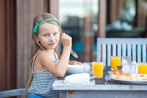 garota tomando café da manhã em um café ao ar livre