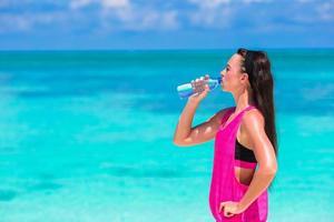 mulher bebendo água perto do oceano foto