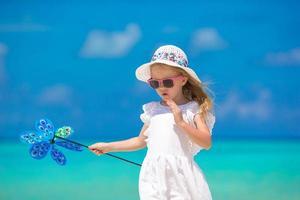 menina de chapéu segurando um cata-vento na praia