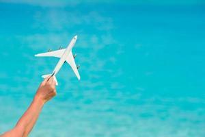 avião de brinquedo contra um mar turquesa