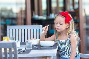 garota comendo mingau em um café ao ar livre