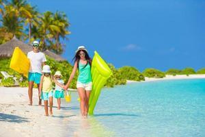 família de quatro pessoas em férias na praia foto