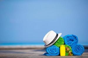 toalhas, chapéu e protetor solar na praia