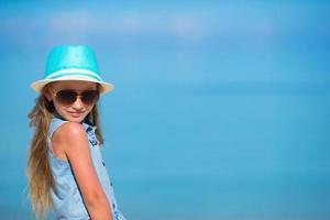 menina de chapéu e óculos escuros na praia
