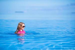 menina nadando na piscina foto