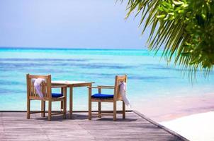 mesa e cadeiras de madeira com laços brancos