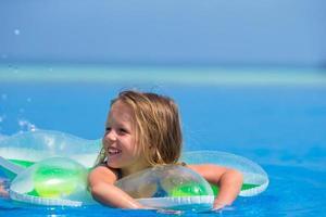 garota em um floatie em uma piscina foto