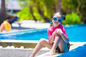 menina sentada na beira de uma piscina foto