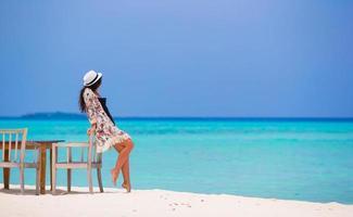 mulher encostada em uma cadeira na praia