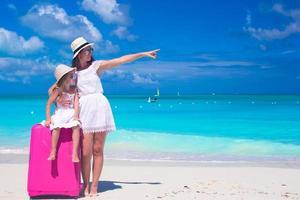 mãe e filha com bagagem em uma praia tropical