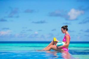 mulher sentada na beira de uma piscina