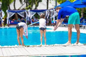 maldivas, sul da ásia, 2020 - pai ensinando suas filhas a mergulhar em uma piscina foto