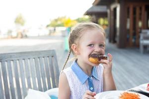 menina comendo um donut