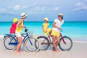 família se divertindo andando de bicicleta na praia