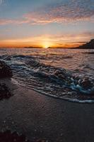 dramático pôr do sol sobre o mar foto