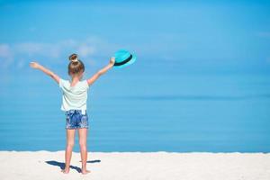 menina segurando chapéu na praia