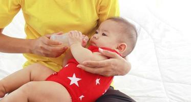 mãe alimentando um bebê com mamadeira