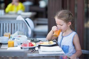 menina bebendo suco no café da manhã