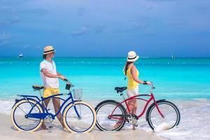 casal com bicicletas em uma praia de areia branca