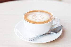 xícara de café com latte art nela foto