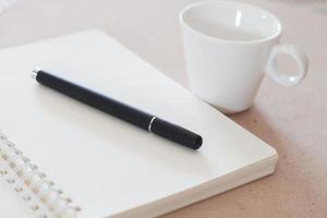 caneta e caderno com uma xícara de café branca