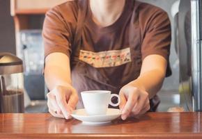 barista oferecendo uma xícara de café branco foto