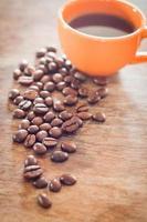 grãos de café com uma xícara de café