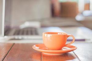 xícara de café laranja em uma estação de trabalho foto