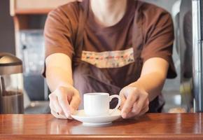 barista oferecendo mini xícara de café branco foto