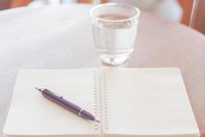 caderno aberto e caneta com água