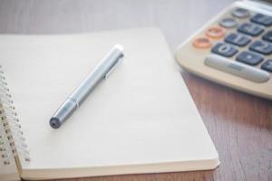 caderno com uma caneta e uma calculadora foto