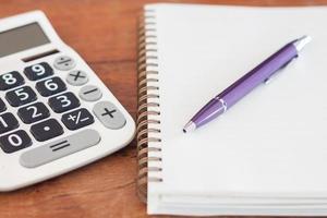 caneta roxa e caderno com calculadora