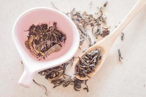 chá oolong em colher de pau e xícara de cerâmica