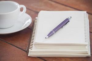 caneta roxa e caderno com uma xícara de café