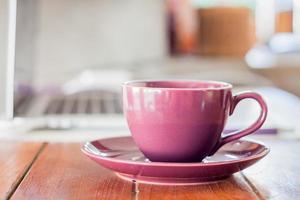 xícara de café roxa em uma estação de trabalho