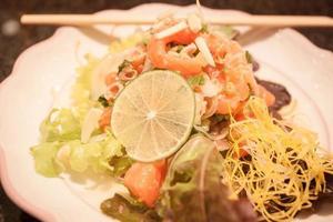salada picante de salmão em prato branco foto
