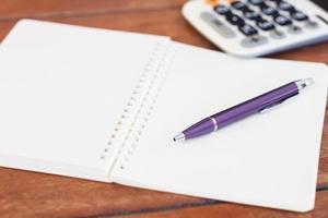caneta roxa em um caderno aberto